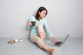 Happy casual beautiful asian woman working on a laptop sitting o Royalty Free Stock Photo