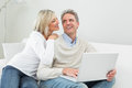 Happy casual couple using laptop at home in the living room Royalty Free Stock Photography