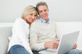 Happy casual couple using laptop at home in the living room Stock Images