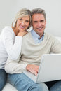 Happy casual couple using laptop at home portrait of a in the living room Stock Image