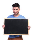 Happy casual man showing a blank board on white background Stock Image