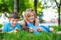 Happy caucasian family in park laying the grass with apple Royalty Free Stock Photo