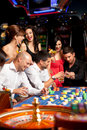Happy caucasian friends playing roulette in casino Stock Image