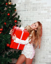Happy caucasian woman blond with red gift near christmas tree studio shot Royalty Free Stock Images
