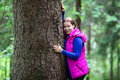 Happy caucasian woman embracing with huge tree in evergreen forest Stock Images