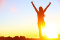 Happy celebrating winning success woman sunset at or sunrise standing elated with arms raised up above her head in celebration of Stock Photos