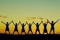 Happy celebrating women at sunset or sunrise standing elated with arms raised up above their heads Stock Photo