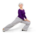 Happy charming beautiful elderly woman doing exercises while working out playing sports