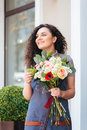 Happy charming young woman florist holding flower bouquet near shop Royalty Free Stock Photo