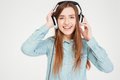 Happy charming young woman in headphones listening to music portrait of over white background Stock Image