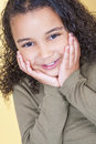 Happy cheeky african american mixed race girl child studio shot of a beautiful young smiling and looking with hands on her face Royalty Free Stock Images