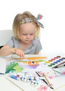 Happy cheerful baby girl child drawing with brush in album with Royalty Free Stock Photo