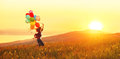 Happy cheerful girl with balloons running across meadow at sunse Royalty Free Stock Photo