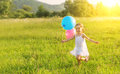 Happy cheerful girl playing and having fun with balloons in the summer little running around on nature Royalty Free Stock Images
