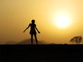 Happy cheerful independent girl silhouette of a slender little and teen standing lonely against the sunset golden yellow hues make Stock Images