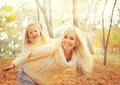 Happy cheerful mother holding smiling baby girl and play  together in sunny autumn park. Royalty Free Stock Photo
