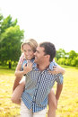Happy and cheerful young caucasian couple piggybacking outdoors green summer forest environment vertical image Stock Photography