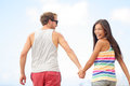 Happy cheerful young trendy couple holding hands walking together outside smiling having fun being in love beautiful Royalty Free Stock Image