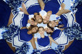 Happy cheerleaders forming huddle against sky directly below shot of Royalty Free Stock Images