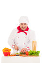 Happy chef cooking with fresh vegetables wearing red and white uniform over background Stock Photos