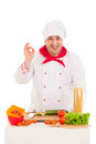 Happy chef cooking with fresh vegetables wearing red and white uniform over background Royalty Free Stock Image