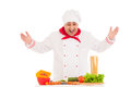 Happy chef cooking with fresh vegetables wearing red and white uniform over background Royalty Free Stock Photography