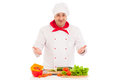 Happy chef cooking with fresh vegetables wearing red and white uniform over background Stock Photo