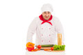 Happy chef cooking with fresh vegetables wearing red and white uniform over background Stock Image