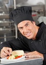 Happy chef garnishing dish portrait of male in commercial kitchen Royalty Free Stock Images