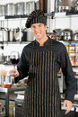 Happy chef holding glass of red wine portrait young male at commercial kitchen Stock Photo