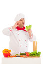 Happy chef holding leaf of salad and cooking with fresh vegetabl vegetables wearing red white uniform over white background Stock Photo