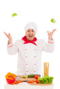 Happy chef holding leaf of salad and cooking with fresh vegetabl vegetables wearing red white uniform over white background Stock Images