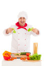 Happy chef holding leaf of salad and cooking with fresh vegetabl vegetables wearing red white uniform over white background Stock Image