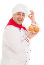 Happy chef holding plate with muffins wearing red and white un uniform over background Stock Images