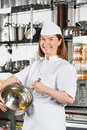 Happy chef mixing egg with wire whisk in bowl portrait of female at commercial kitchen Royalty Free Stock Photos