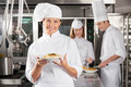 Happy chef presenting dish in industrial kitchen portrait of female with colleagues working Royalty Free Stock Image
