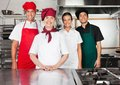 Happy chefs standing together in kitchen portrait of female mature chef with colleagues commercial Royalty Free Stock Photos
