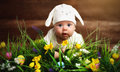 Happy child baby dressed as the Easter bunny rabbit on the grass