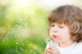Happy child blowing dandelion outdoors in spring park Royalty Free Stock Photo