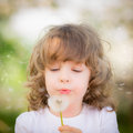 Happy child blowing dandelion outdoors in spring park Royalty Free Stock Images