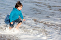 Happy child caught by waves wetting the clothes while escaping the in winter Stock Images