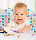 Happy child draws with colored pencils crayons baby Stock Image