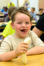 Happy child eating healthy lunch in school cafeteria busy Stock Photography