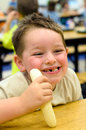 Happy child eating healthy lunch in school cafeteria busy Stock Images