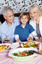 Happy child eating little with his grandparents at the dinner table Royalty Free Stock Image