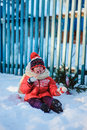 Happy child girl with christmas decorations at wooden fence in winter, cozy country style holidays Royalty Free Stock Photo