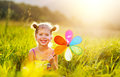 Happy child girl with colorful pinwheel windmill in summer Royalty Free Stock Photo