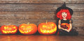 Happy child girl in costume witch for Halloween with pumpkins Royalty Free Stock Photo