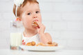 Happy child  girl eats cookies and milk Royalty Free Stock Photo