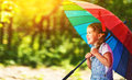 Happy child girl laughs and plays under summer rain with an umbrella Royalty Free Stock Photo